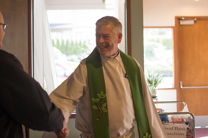 Pastor Gary Delanius greets someone before worship at Holy Cross in Bellevue